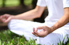Young man during relaxation and meditation in park meditation se. Ssion. Frame shows half of body Stock Photos