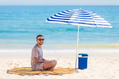 Young man relaxes on the beach under umbrella with laptop surf in internet. The man relaxes on the beach under umbrella with laptop surf in internet stock photos