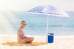 Young man relaxes on the beach under umbrella with laptop surf in internet. The man relaxes on the beach under umbrella with laptop surf in internet stock images
