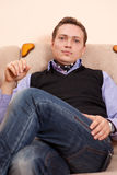 Young man relaxing in armchair Stock Image