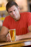 Young man relaxing at a bar with a beer Stock Image