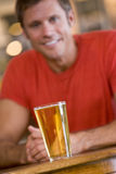 Young man relaxing at a bar with a beer Royalty Free Stock Image