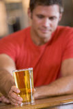Young man relaxing at a bar with a beer Stock Photos