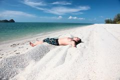 Young man relaxing on the beach. Stock Image