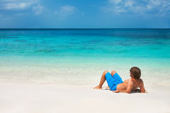Young man relaxing on the beach Stock Photos