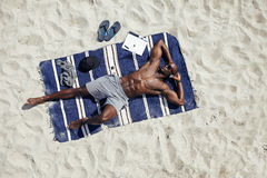 Young man relaxing on the beach Royalty Free Stock Photos