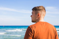 Young man relaxing on beach looking aside.  Stock Images