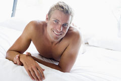 Young man relaxing in bed. Smiling Royalty Free Stock Images