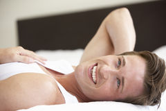 Young Man Relaxing On Bed Stock Photography