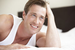 Young Man Relaxing On Bed Royalty Free Stock Photos