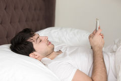 Young man relaxing in bed at home using mobile smartphone royalty free stock photos