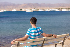 Young man relaxing on bench on the beach Royalty Free Stock Images