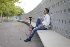 Young man biker relaxing on a bench while listening music stock photo