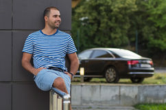 Young man relaxing with car background Royalty Free Stock Photos