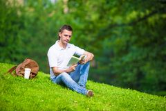 Young man relaxing with coffee in park reading a Stock Image