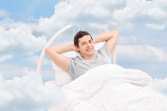 Young man relaxing on a comfortable bed Royalty Free Stock Photo