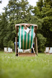 A young man relaxing on a deckchair in St James Park, holding a guidebook Royalty Free Stock Images