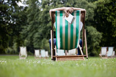 A young man relaxing on a deckchair in St James Park, holding a guidebook Stock Images