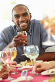 Young Man Relaxing At Dinner Party. Smiling At Camera Whilst Holding Glass Of Wine Royalty Free Stock Image