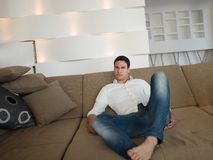 Young man relaxing and dreaming on sofa at home Royalty Free Stock Photos