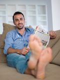 Young man relaxing and dreaming on sofa at home stock photo