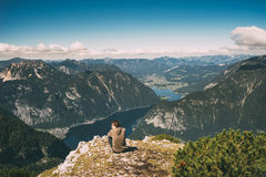 Young man relaxing on the edge of mountain and enjoying wonderfu Stock Photo