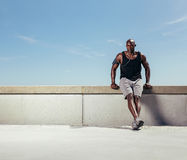 Young man relaxing on embankment after his run Royalty Free Stock Image