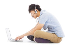 Young man relaxing on floor and listening to music. In studio Royalty Free Stock Image