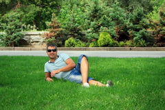 Young man relaxing on the green grass Stock Images