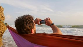 Young man relaxing in hammock on a beach and taking photo of sea with mobile phone. Hd slowmotion. Crimea, Russia. Young man relaxing in hammock on a beach and stock video