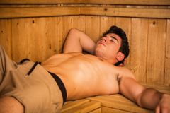Young Man Relaxing with Hand Behind Head in Sauna Stock Image