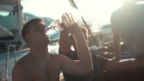 Young man relaxing happily on the vacation sailboat yacht and drinking water. Having a rest on summer boat. Slow motion stock footage