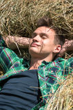Young man relaxing in haystacks Stock Photo
