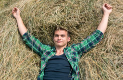 Young man relaxing in haystacks Royalty Free Stock Photography