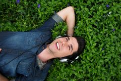 Young man relaxing with headphones outdoors - from above Royalty Free Stock Photography