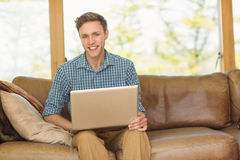 Young man relaxing on his couch with laptop Royalty Free Stock Photo