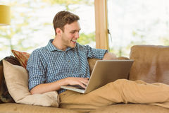 Young man relaxing on his couch with laptop Royalty Free Stock Photos