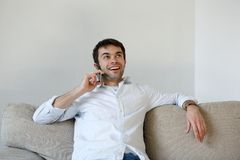 Young man relaxing at home calling by mobile phone Royalty Free Stock Photos
