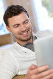 Young man relaxing at home using tablet Stock Photography