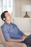 Young Man Relaxing Listening To Music At Home Royalty Free Stock Image