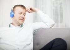 Young man relaxing listening to music Stock Image
