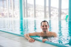 Young man relaxing on a luxury rooftop swimming pool and smiling at camera at five star hotel spa Stock Photo