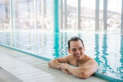 Young man relaxing on a luxury rooftop swimming pool and smiling at camera at five star hotel spa Stock Images