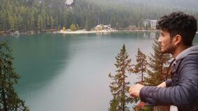 Young man relaxing at mountain lake. Handsome yung man standing by mountain lake, on background of woods looking away. Braies lake or Pragser Wildsee in Trentino stock footage