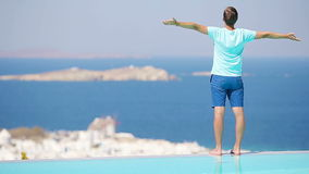 Young man relaxing near pool with amazing view on Mykonos, Greece