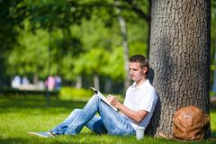 Young man relaxing near tree with coffee reading a Stock Images