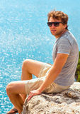 Young Man relaxing Outdoor on rocky cliff sitting and looking on Stock Photography