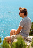 Young Man relaxing Outdoor on rocky cliff sitting and looking on Sea Royalty Free Stock Photo