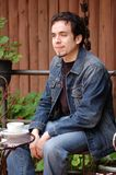 Young Man Relaxing Outdoors. A young man enjoy and having a cup of coffee outside Stock Photo