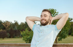 Young man relaxing on park bench Royalty Free Stock Photo